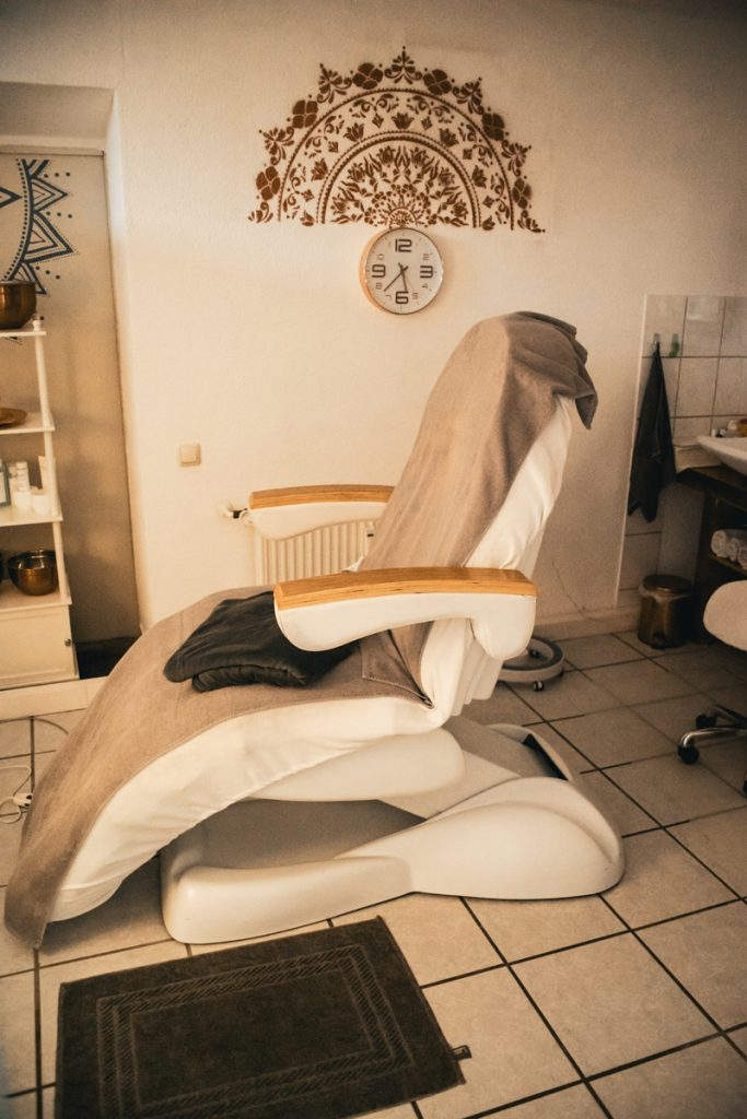 Behandlungsliege mit Decke von SkinSense. Im Hintergrund eine Wanduhr und ein an die Wand gemaltes Mandala