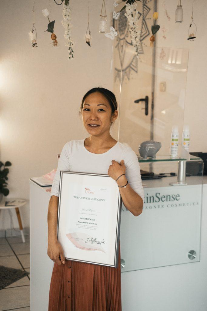 Bild von SkinSense Inhaberin Sarah Wagner, die ihr gerahmtes Permanent Make Up Zertifikat in den Händen hält